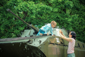 Mom takes pictures of his son on vintage military vehicle.