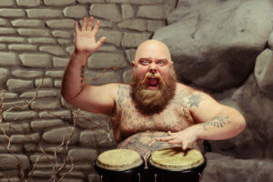 Music is his soul. Portrait of funny bearded shirtless man with tattooed body playing the drum with inspiration while sitting against stonewall background