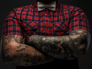 Portraite of brutal hipster with tattooes on his hand dressed in red shirt and bow tie.