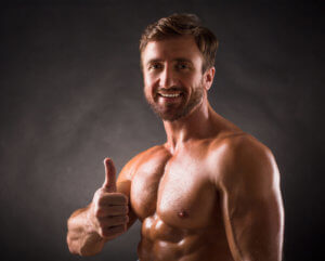 Portrait of shirtless mascular man showing thumb-up over dark grey background. Happy bodybuilder smiling for the camera.