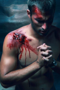 Portrait of handsome masculine bleeding man with a Blood on his shoulder Face and lips wearing jeans and watch who praying and look like Catholic